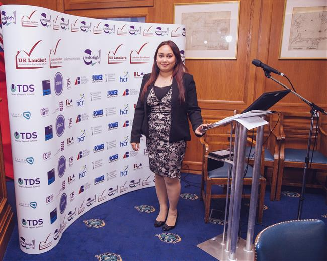 Fatima standing proud with all the company logos that have sponsored the event
